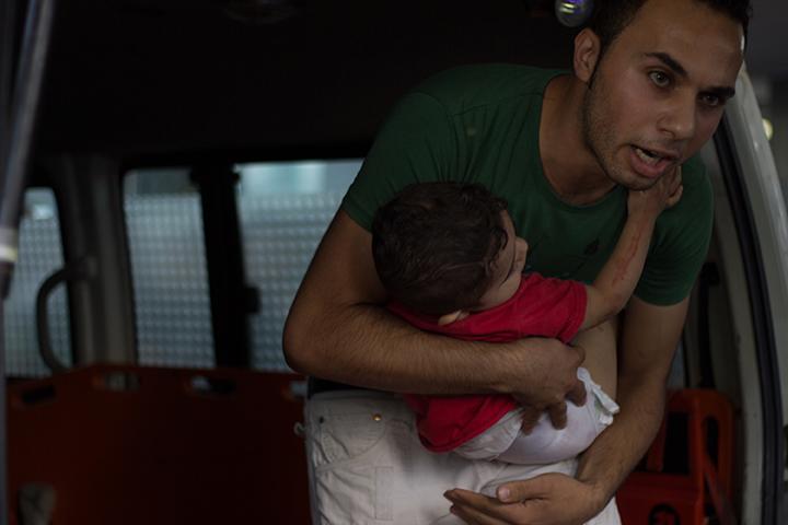 Un palestinien tenant un bébé blessé lors des massacres de 2014_1