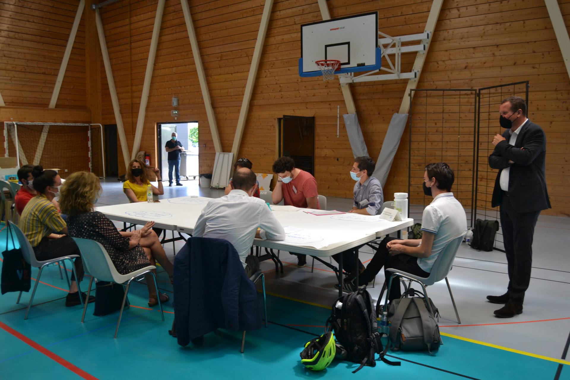 Des personnes masquées sont assises autour d'une table dans un gymnase