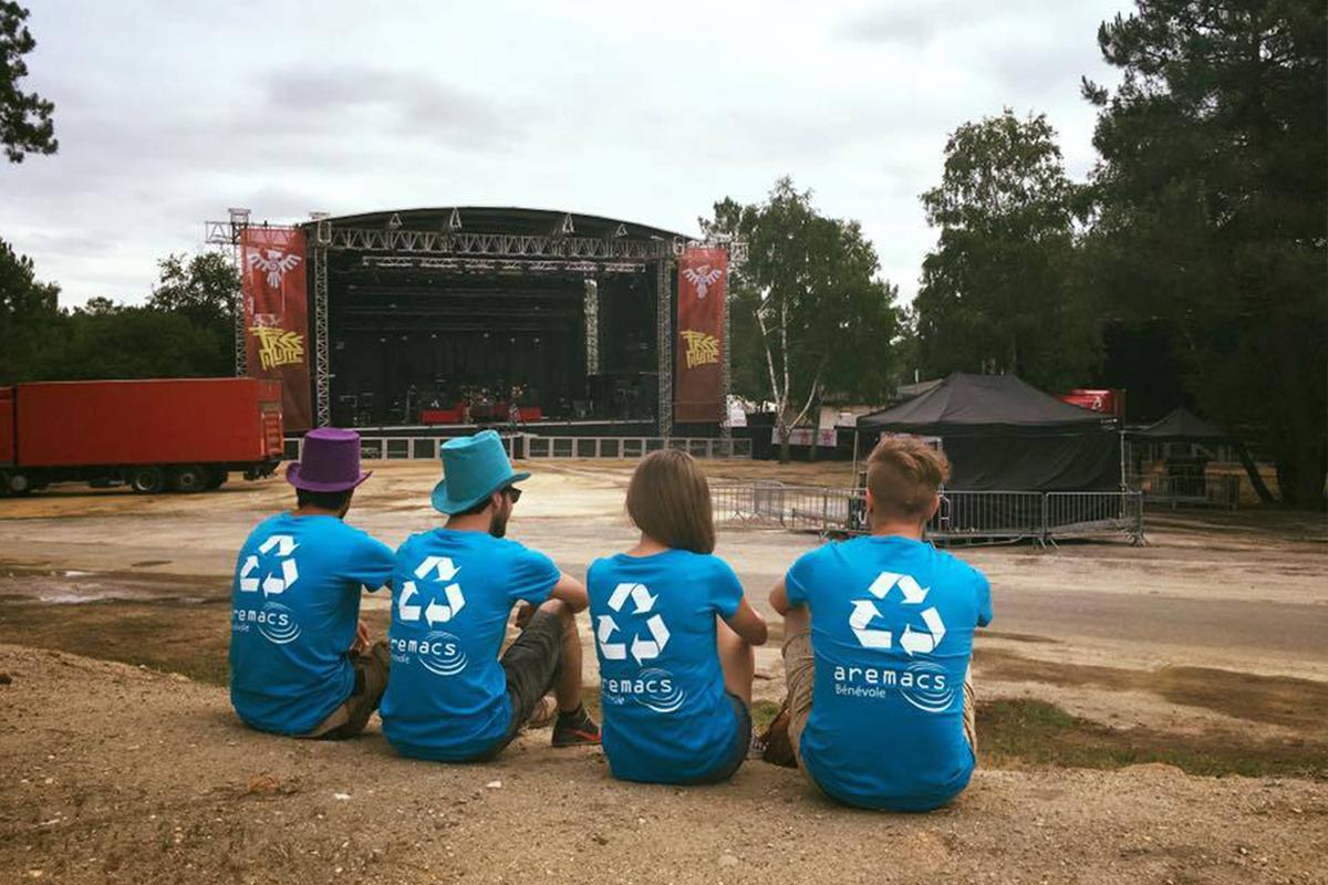 Bénévoles d'Aremacs devant une scène de festival.